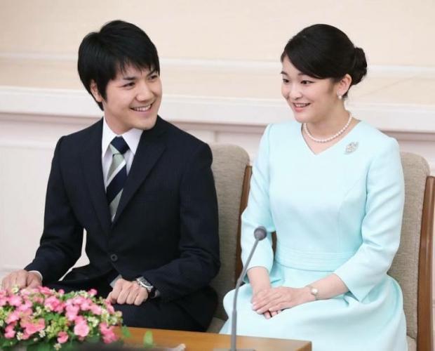 Принцесса Мако в голубом платье сидит вместе с женихом