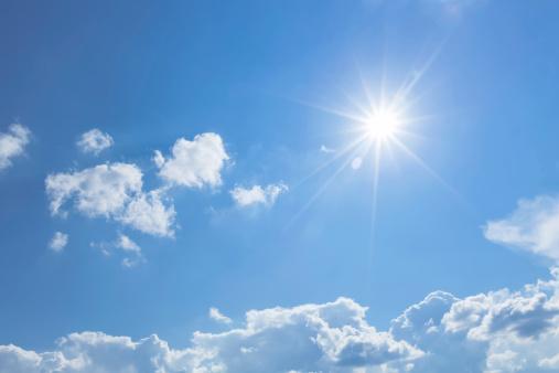 солнце на голубом небе с легкими белыми облаками
