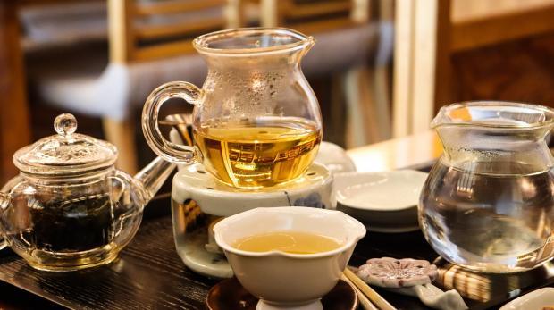 стеклянные заварник, чайник и чашки с чаем