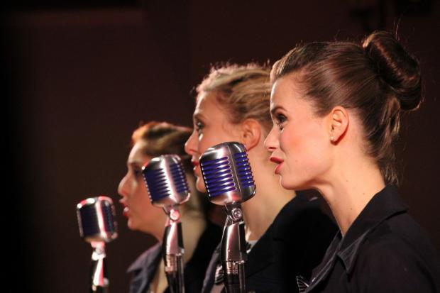 Три девушки поют в микрофоны