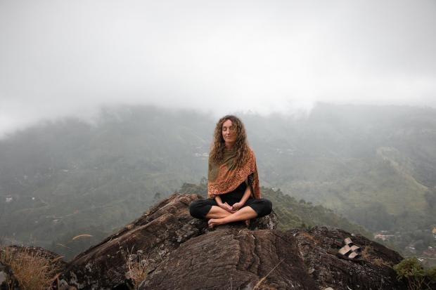 девушка медитирует на вершине горы