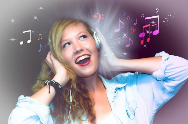 смеющаяся девушка в наушниках слушает музыку