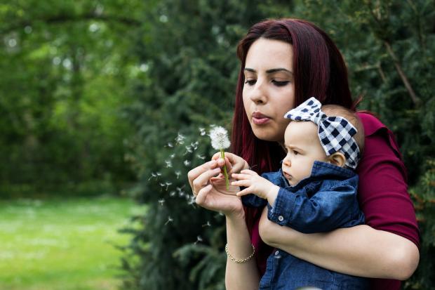 Молодая мама с маленьким ребенком дуют на одуванчик