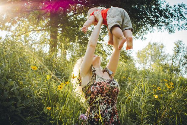 Женщина в цветастом платье держит на руках маленького ребенка