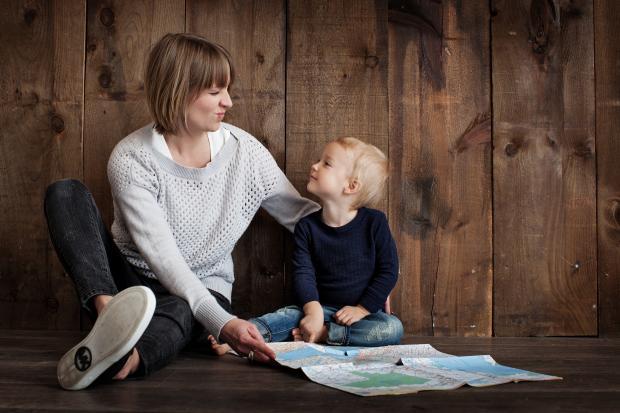 Женщина в белой рубашке сидит с ребенком на полу
