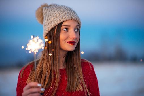 девушка в шапке стоит с бенгальской свечой в руке
