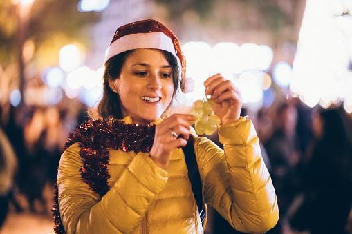 девушка в колпаке Деда Мороза встречает Новый год