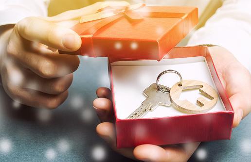 в красной коробочке лежит ключи с брелком в виде дома