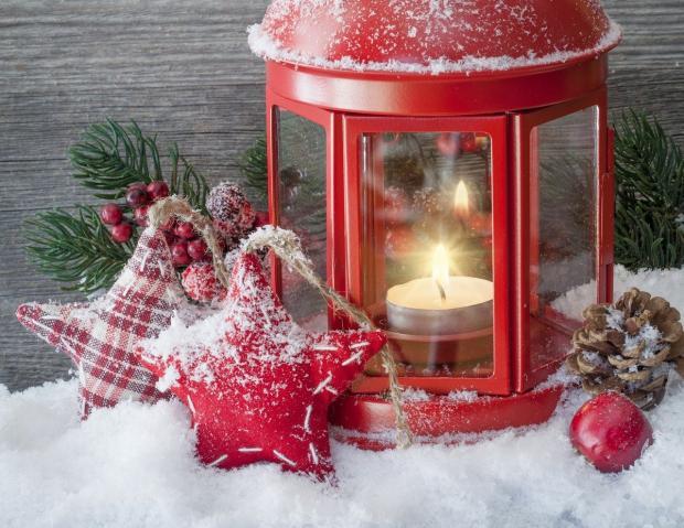 красный рождественский фонарь с горящей свечой внутри