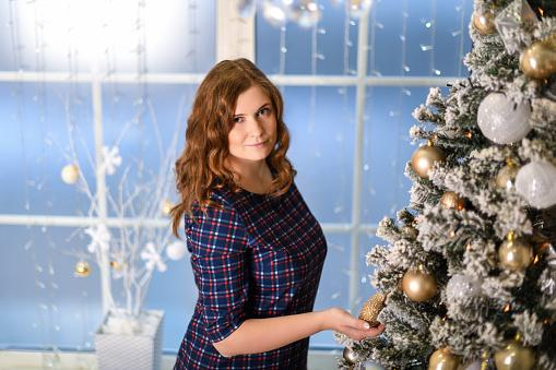 девушка с каштановыми волосами стоит рядом с наряженной новогодней елкой