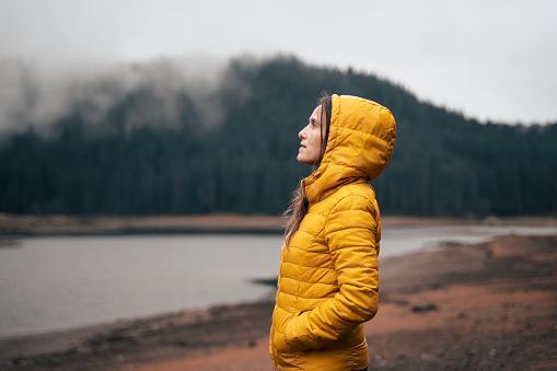 девушка в желтой куртке на берегу реки