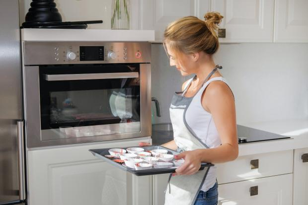 Девушка с противнем возле духовки