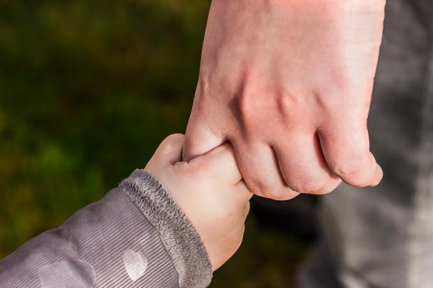 ребенок держится за палец взрослого