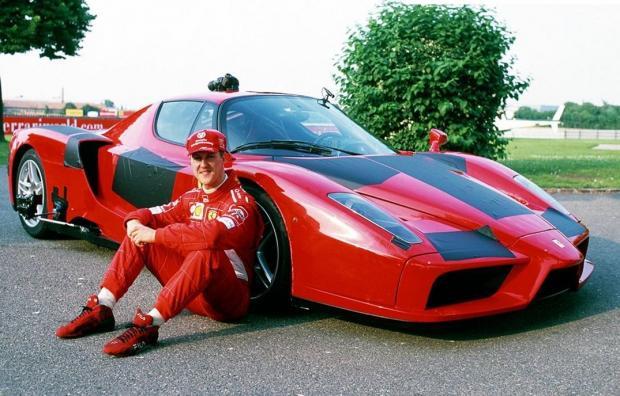 Михаэль Шумахер сидит возле машины
