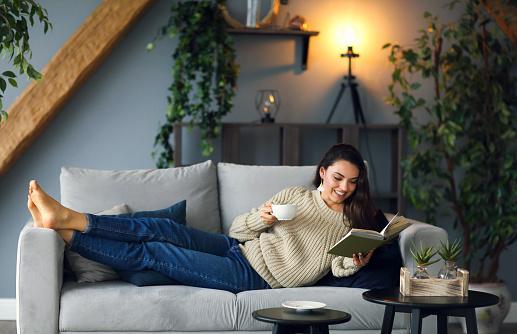 девушка лежа читает на белом диване с чашкой чая в руках