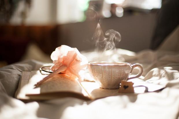 дымящаяся чашка с чаем на книге стоит