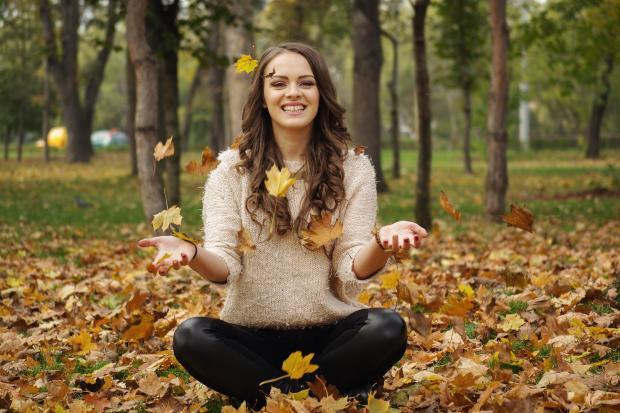 девушка сидит на листве и улыбается