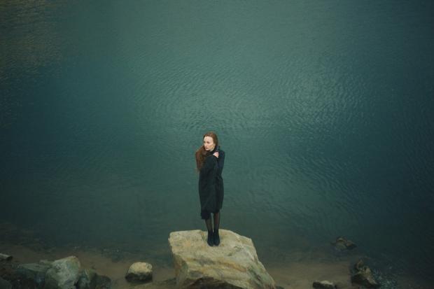 девушка стоит одиноко на берегу водоема