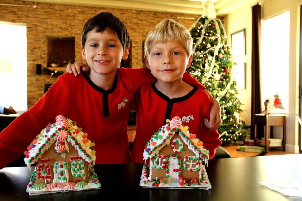 два мальчика стоят рядом с рождественскими пряничными домиками