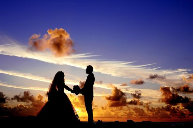 молодожены стоят на фоне закатного неба