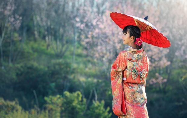 молодая японка в национальном костюме под зонтиком стоит на фоне природы