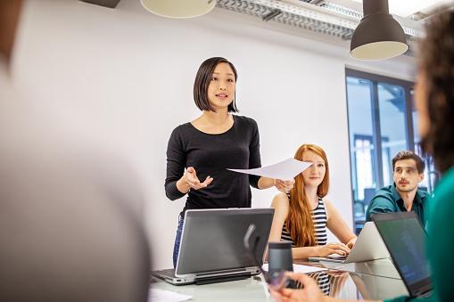 девушка выступает в офисе с докладом
