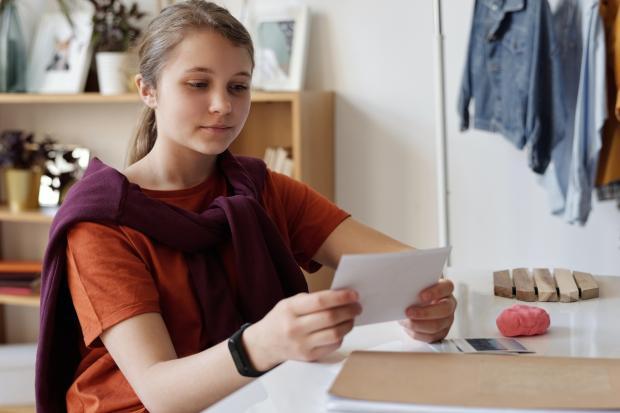 Девушка в красной футболке держит в руках фотографию