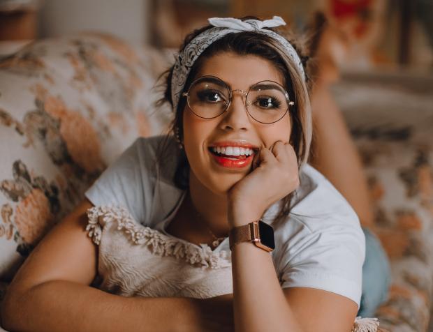 Девушка в очках и повязке на голове лежит на диване