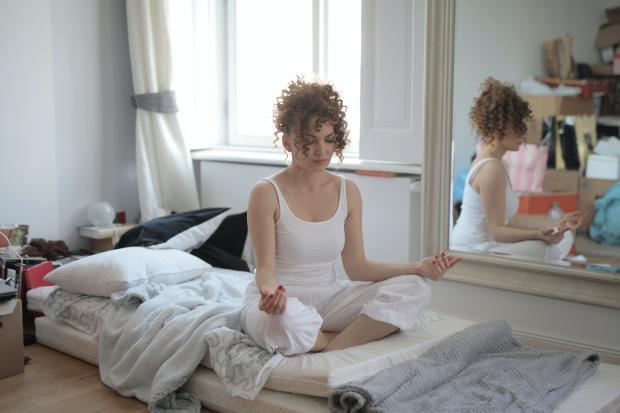 Кудрявая девушка в белой пижаме сидит на кровати