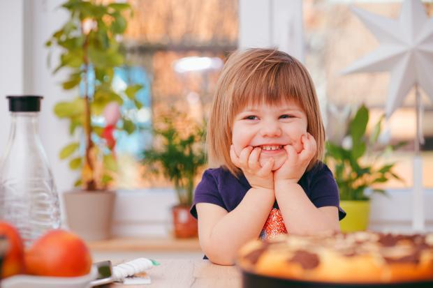 Маленькая девочка улыбается сидя за столом
