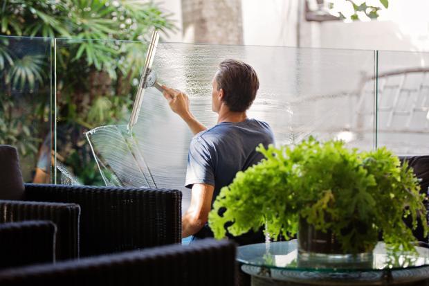 Молодой парень моет окно