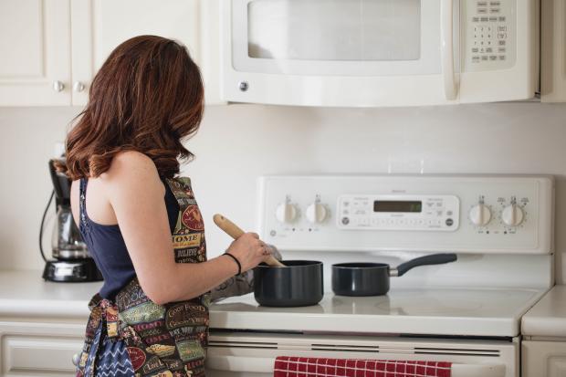 Девушка в фартуке готовит еду на кухне