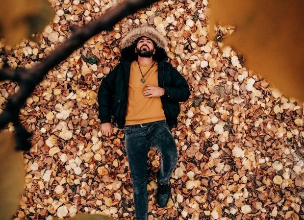 Молодой мужчина в светлом свитере и теплой куртке лежит на земле покрытой листьями