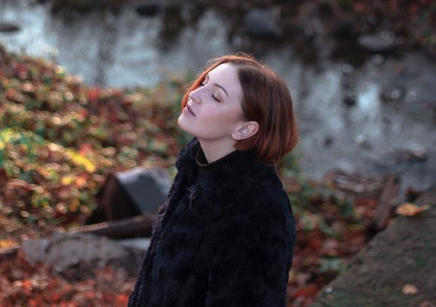 Девушка с короткой стрижкой в черном пальто стоит в лесу