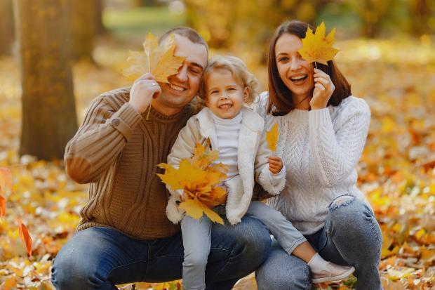 Семья в теплой одежде в осеннем парке держит желтые листья