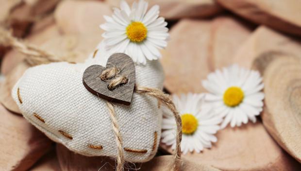 на деревяшках лежит сердце из холщовой ткани и цветки ромашки