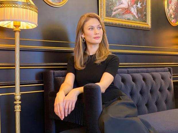 Ольга Куриленко в черных брюках и темной футболке сидит на диване