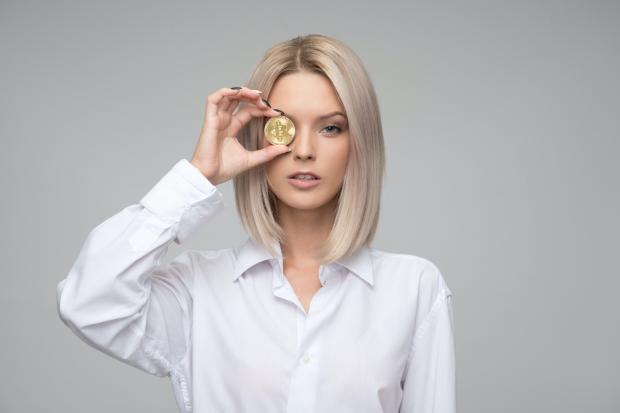 Блондинка в белой блузе держит возле лица золотую монету