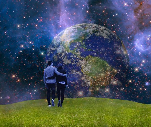 парень и девушка стоят обнявшись перед планетой Земля