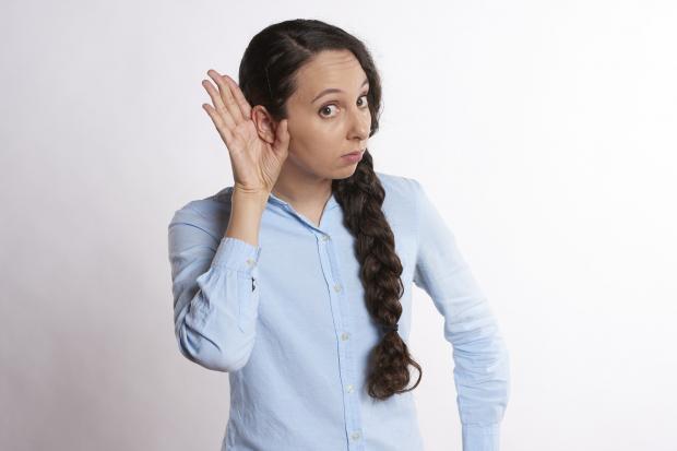 девушка с длинной косой приставила руку к уху