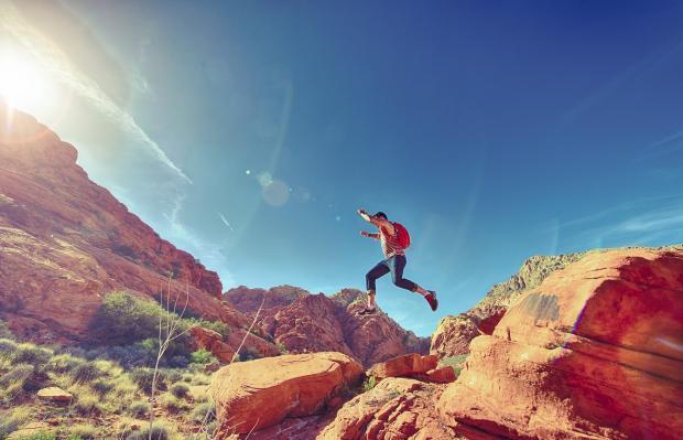 человек перепрыгивает с камня на камень