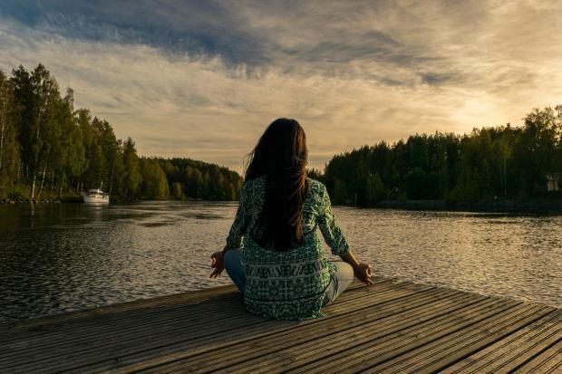девушка сидит на деревянном пирсе у реки и медитирует