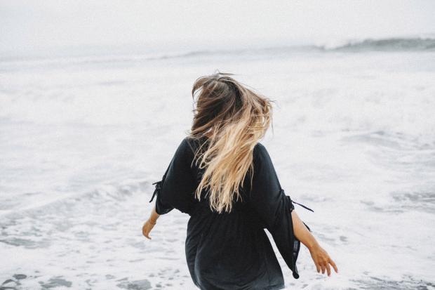 Девушка со светлыми волосами в черном платье бежит по пляжу