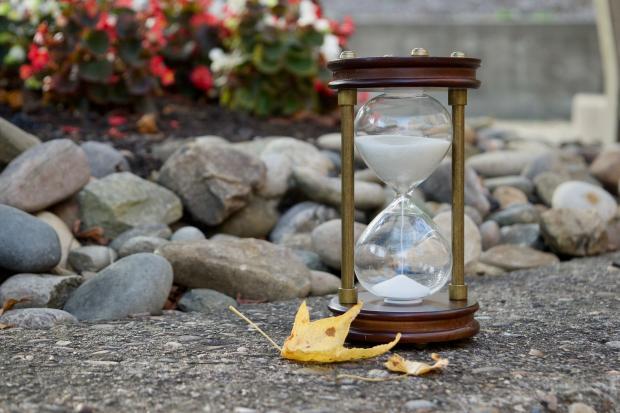 песочные часы, оранжевый листок, камни, цветы