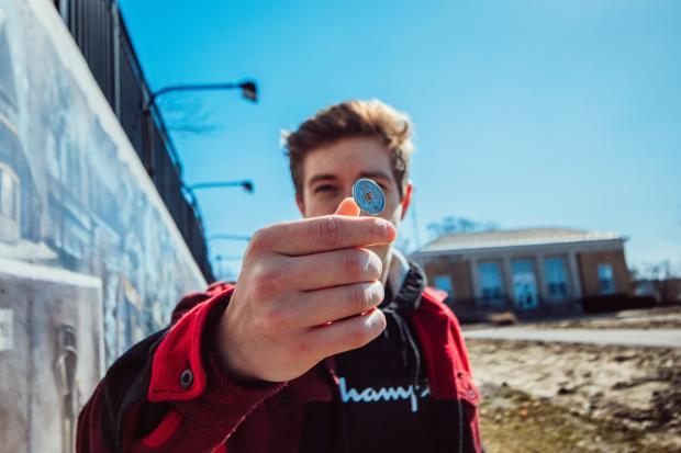 Молодой мужчина держит монету