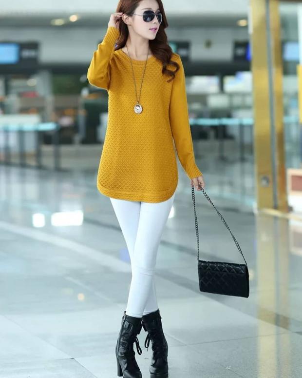 Молодая длинноволосая девушка в белых брюках и желтом свитере