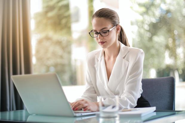 девушка в очках работает перед компьютером