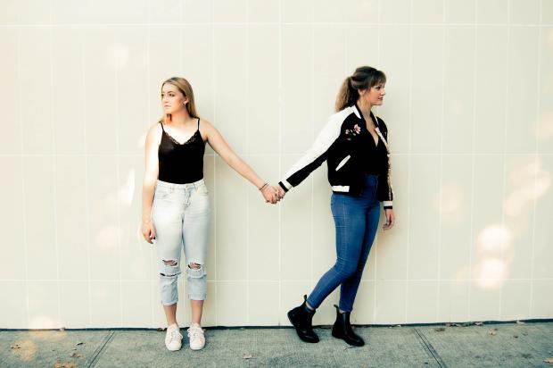 Девушка в черной куртке и синих джинсах держит за руку девушку в светлых брюках и черной майке