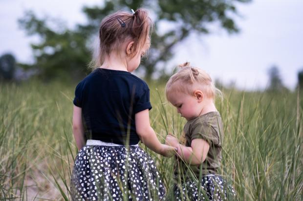 Девочка в черной футболке и юбке держит за руку маленькую девочку