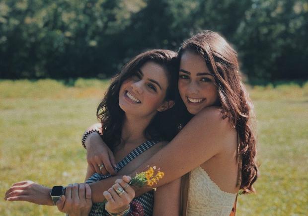 Две длинноволосые девушки обнимаются стоя на поле
